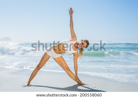 Gorgeous blonde standing in extended triangle pose by the sea on a sunny day - stock photo