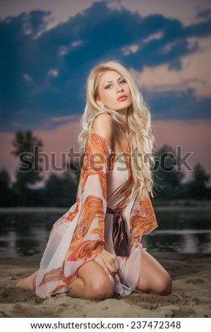 Gorgeous blonde woman in transparent blouse posing provocatively in front of a beautiful sunset. Fair hair girl baring her shoulder and legs in front of lake on cloudy sky background. - stock photo
