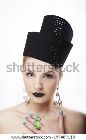Gorgeous blonde woman model with blue eyes and black lipstick wearing big stylish designer black unique hat/ headpiece and unique handmade jewelry. Isolated on white background. Studio closeup