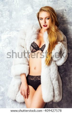 Gorgeous blonde woman posing in luxurious fur coat and lace lingerie. Fashion, beauty. Studio shot. - stock photo