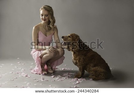 Gorgeous blonde woman sitting on floor next to her cute Golden Spaniel dog. - stock photo