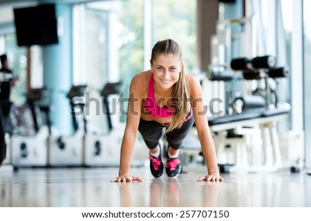 Gorgeous blonde woman warming up and doing some push ups a the gym - stock photo