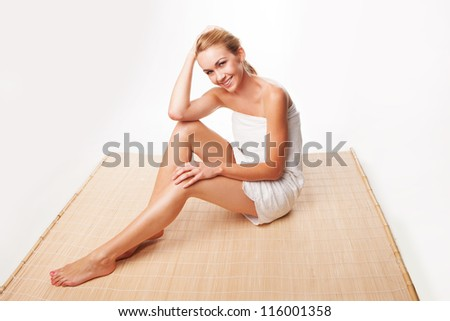 Gorgeous blonde woman wrapped in a towel sitting on a reed mat with long shapely legs and a beautiful smile as she relaxes after a beauty treatment - stock photo