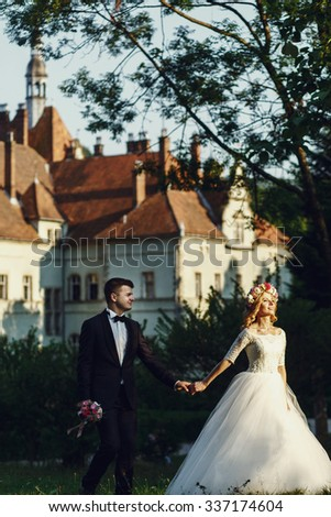 Gorgeous blonde young bride and charming groom holding hands at sunset fairy-tale castle background - stock photo