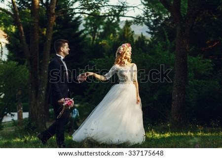 Gorgeous blonde young bride and charming groom holding hands at sunset in forest background - stock photo