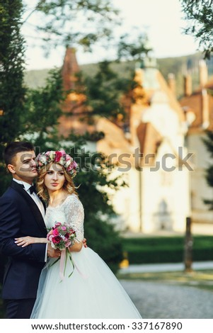 Gorgeous blonde young bride and charming groom posing at sunset fairy tale castle background - stock photo