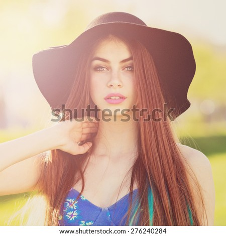 Gorgeous bohemian styled fashionable young woman in blue floral dress and fedora hat posing. Closeup portrait of trendy blue eyed redhead girl with makeup. Retouched, filter applied, square format. - stock photo