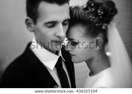 gorgeous bride and stylish groom gently hugging at sandy beach lake, beautiful moment, black and white photo - stock photo