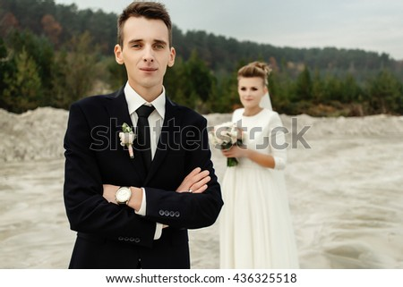 gorgeous bride and stylish groom holding hands and looking at sandy beach lake, true emotions, luxury wedding - stock photo