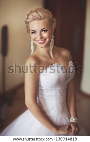 Gorgeous bride blonde in wedding dress in luxury interior with diamond jewelry posing at home and waiting for groom. Romantic rich happy girl in bridal dress smiling have final preparation for wedding - stock photo