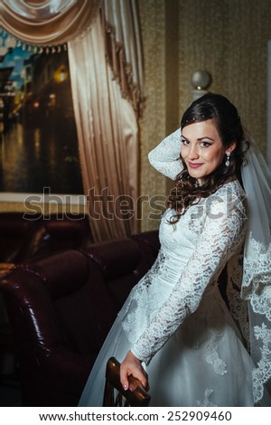Gorgeous bride blonde in wedding dress in luxury interior with diamond jewelry posing at home and waiting for groom. Rich brunette bride in a luxurious wedding dress in elegant expensive interior - stock photo