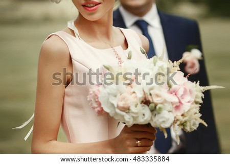 gorgeous bride holding wedding bouquet of pink flowers, smiling, and groom on background, tender romantic sensual moment at botanical garden