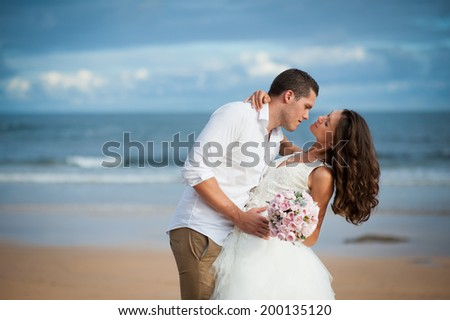 Gorgeous bride in a wedding dress and a handsome groom getting married at a beautiful beach