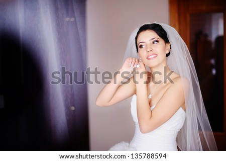 Gorgeous bride is getting ready at home - stock photo