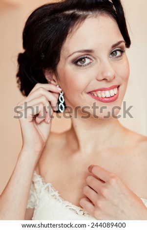 Gorgeous bride on her wedding day, wear earrings, morning bride