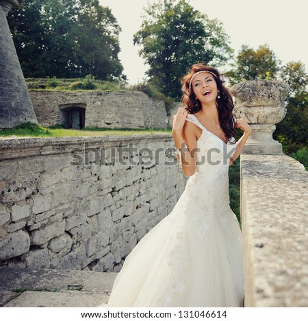 gorgeous bride outdoors bursts of laughing - stock photo