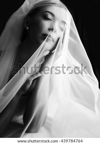 Gorgeous bride sits with closed eyes and holds her face with arms under a veil - stock photo