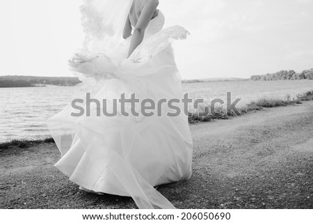 Gorgeous bride spinning around in wedding dress. - stock photo