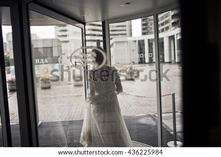 Gorgeous bride walks out of the hotel through the glass door - stock photo