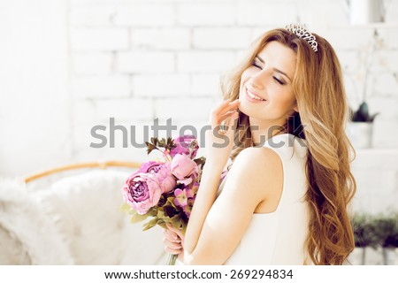 Gorgeous bride with wedding bouquet makeup and hairstyle in bridal dress at home waiting for groom. - stock photo