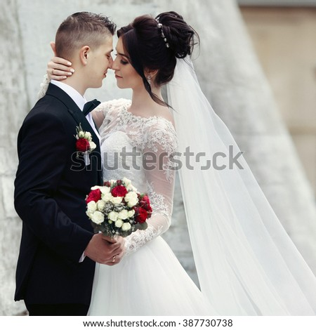 Gorgeous brunette bride hugging groom and posing near old castle wall closeup - stock photo