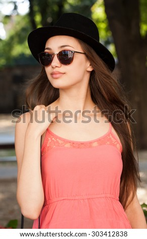Gorgeous brunette model woman outdoors wearing pink summer dress. - stock photo