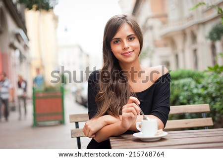 Gorgeous brunette tourist girl having coffee on the street.