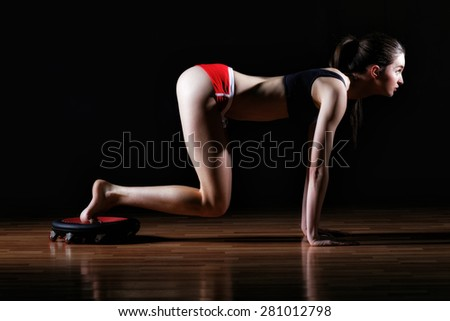 Gorgeous brunette warming up and doing some push ups a the gym. Attractive fitness woman, trained female body, lifestyle portrait, caucasian model. - stock photo