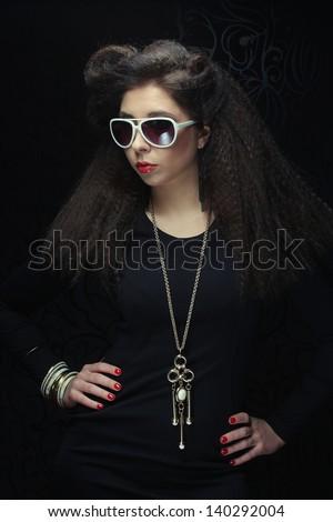 gorgeous brunette wearing sunglasses posing in the studio - stock photo