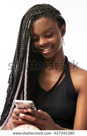 Gorgeous brunette woman, afro descendant, with long and braided hair, using a cell phone, and smiling. She is an elegant Brazilian woman, isolated in a white background. - stock photo