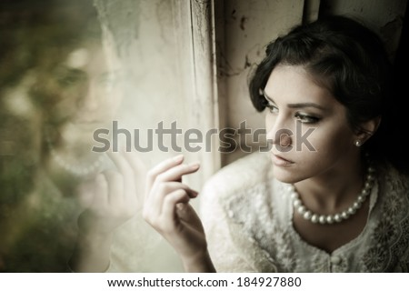 Gorgeous brunette woman with brown eyes wearing pearls looking through the window portrait - stock photo