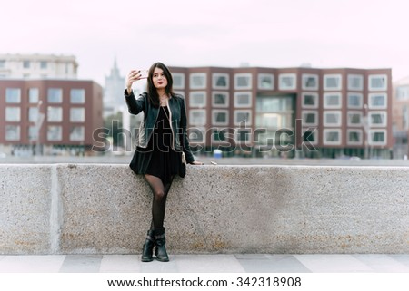 Gorgeous brunette women dressed in cool stylish clothes making self portrait with mobile phone camera, young Caucasian female tourist posing while photographing herself for social network picture  - stock photo