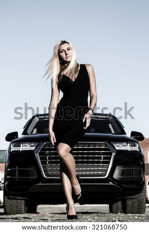 Gorgeous business lady at the background of the modern luxury car - stock photo
