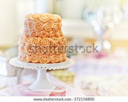 Gorgeous cake covered in roses made of butter cream icing sitting on a cake pedestal with a bokeh background - stock photo