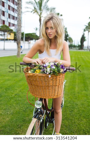Gorgeous caucasian female posing outdoors for the camera on her classic bicycle with a basket of beautiful flowers, charming women cyclist enjoying rest after riding on vintage bike in beautiful park - stock photo