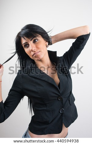 Gorgeous Caucasian lady with amazing long black hair posing in studio on white background. - stock photo