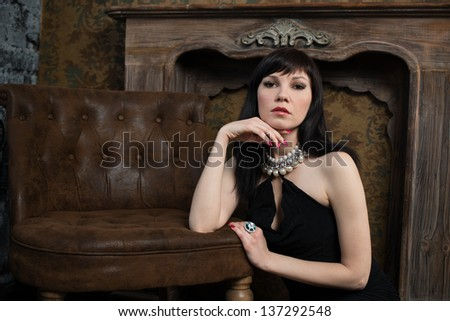 Gorgeous caucasian woman with long dark hair posing in a vintage room, she is wearing black dress and jewelry - stock photo