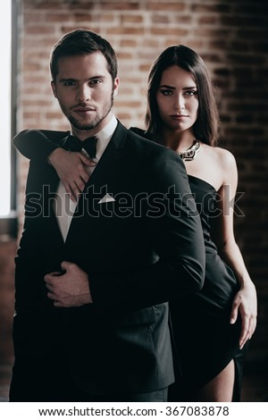 Gorgeous couple. Beautiful young woman standing behind her boyfriend wearing suit and looking at camera while both standing against brick wall - stock photo