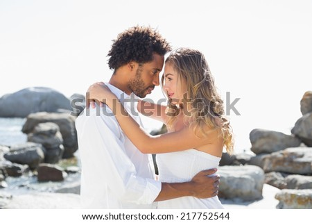 Gorgeous couple embracing at the coast on a sunny day - stock photo
