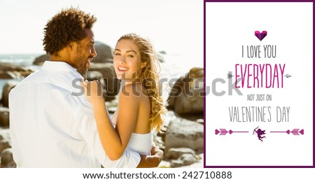 Gorgeous couple embracing by the coast against valentines day greeting - stock photo