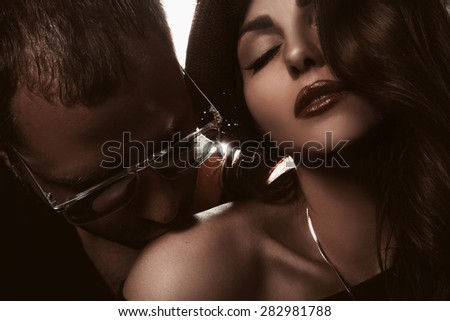 Gorgeous couple in studio. Man kissing shoulder of woman. horizontal photo