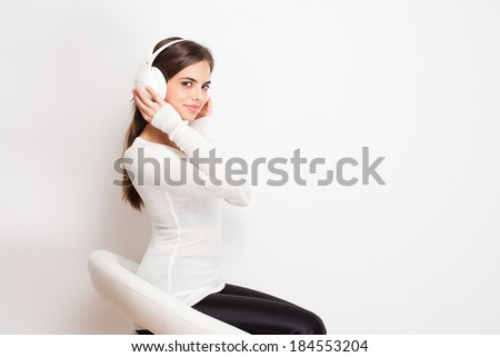 Gorgeous dreamy young brunette woman wearing white headphones. - stock photo