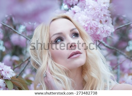 Gorgeous dreamy young woman with long blond hair standing in spring blossom looking up into the air with a faraway expression, close up view of her face - stock photo