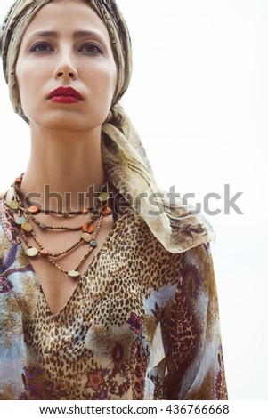 Gorgeous eastern looking up woman standing with nice make-up wearing silk turban, ethnic necklace and luxurious  pareo cover up beachwear. Vintage style. Close up. Outdoor shot