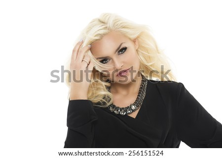 Gorgeous elegant blond woman in a fashionable black dress and necklace flicking her shoulder length hair from her eyes with her hand, isolated on white