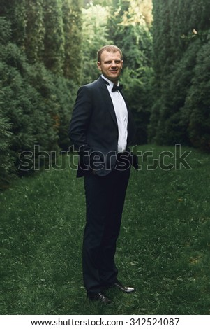 gorgeous elegant luxury stylish groom posing on the background of amazing trees in a park
