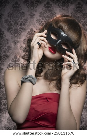 gorgeous elegant woman with red dress, glitter bracelets and stylish hair-style wearing mysterious black mask. Carnival party  - stock photo