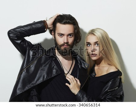 gorgeous fashion beautiful couple in black clothes and posing over white background together. Hipster boy and girl. Bearded young man and blonde model