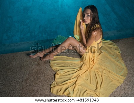 Gorgeous fashion brunette woman in elegant yellow dress sitting beside swimming pool at luxurious villa at night
