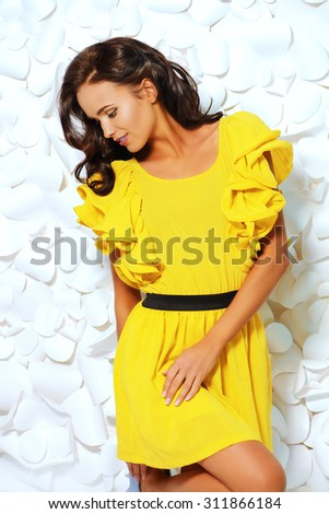 Gorgeous fashion model in bright yellow dress over background of white paper flowers. Beauty, fashion.  - stock photo